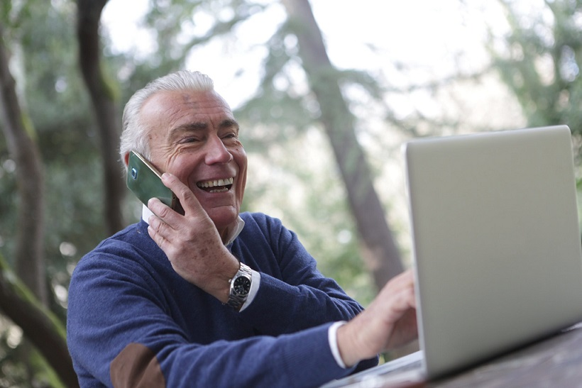 Elderly man taking on the phone and working with a laptop